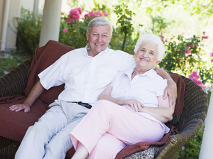 Senior couple relaxing on garden seat looking to  camera