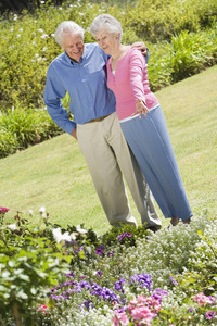 Senior couple standing in garden admiring flowerbed