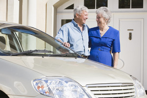 Senior couple standing next to car outside house