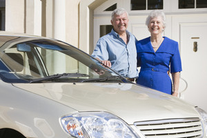 Senior couple standing next to new car outside house