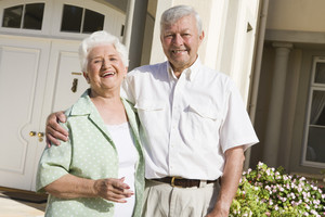 Senior couple standing outside front door of home