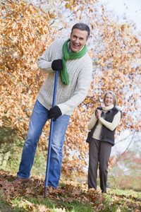 Senior couple tidying autumn leaves in garden