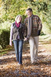 Senior couple walking along autumn path through woods