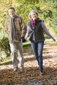 Senior couple walking along path in autumn woods