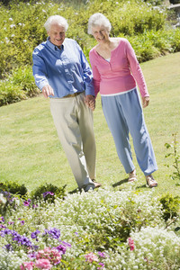 Senior couple walking in garden admiring flowerbeds