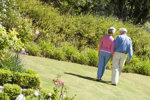 Senior couple walking in garden holding hands