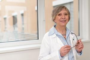 Senior doctor standing in hospital smiling holding her glasses