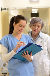 Senior female doctor and young female smiling nurse looking at patient files