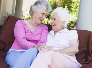 Senior female friends chatting together sitting on garden seat