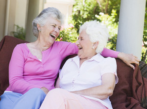 Senior female friends laughing together sitting on garden seat