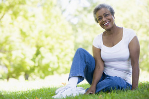 Senior female relaxing in park sitting on grass