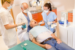 Senior man at dentist surgery having teeth checkup dental assistant