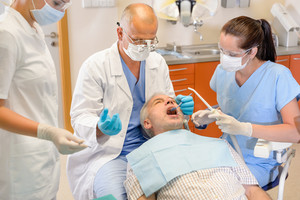 Senior man at dentist surgery having tooth operation stomatology clinic