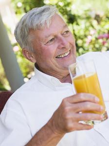 Senior man enjoying glass of juice sitting on garden seat