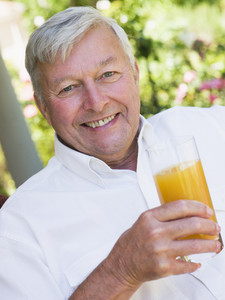 Senior man enjoying glass of orange juice sitting on garden seat