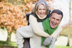 Senior man giving woman piggyback ride through autumn woods