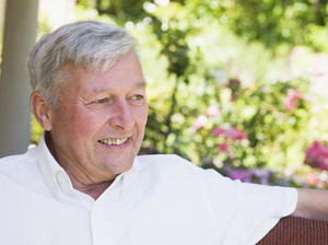 Senior man relaxing at home sitting on garden seat