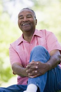 Senior man relaxing in park sitting on grass