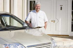 Senior man standing next to new car outside house