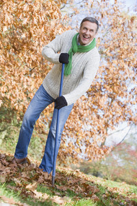 Senior man tidying autumn leaves in garden