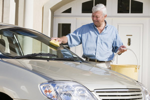 Senior man wasing car with sponge outside house