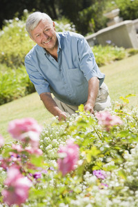Senior man working in garden with trowel
