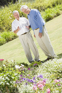 Senior men standing in garden admiring flowerbed