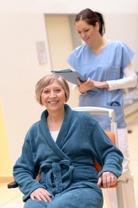 Senior patient in wheelchair smiling,nurse looking at her patient files