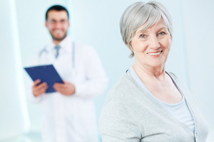 Senior patient looking at camera with doctor on background