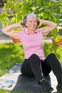 Senior sportive woman exercising on mat doing sit-ups sunny outdoor