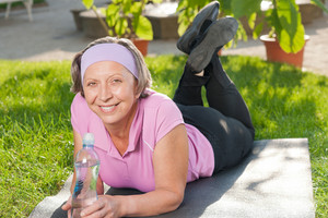 Senior sportive woman lying on mat drink water outside sunny day