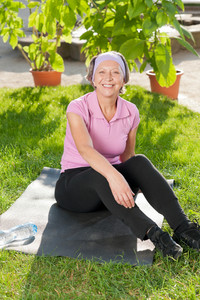 Senior sportive woman sitting on mat outside sunny day