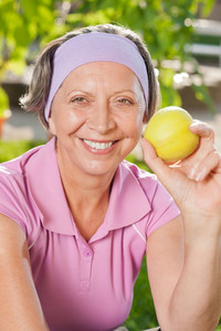Senior sportive woman smiling eat apple outdoor sunny day