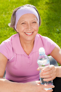 Senior sportive woman smiling relax with water sunny outdoor