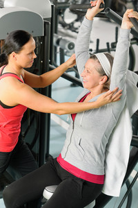 Senior woman at fitness center exercise on machine with trainer