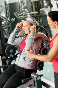 Senior woman at gym exercise with personal trainer on machine