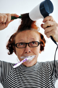 Senior woman brushing teeth and drying hair