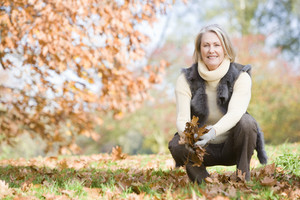 Senior woman collecting autumn leaves on walk