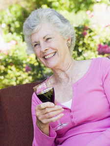 Senior woman enjoying glass of red wine