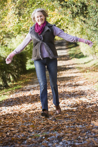 Senior woman enjoying walk through autumn woods
