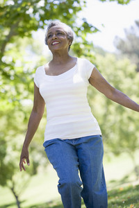 Senior woman exercising outside in park