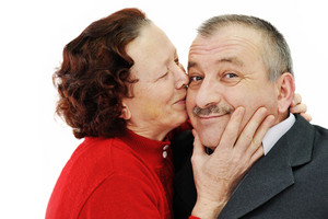 Senior woman kissing in a cheek her husband isolated over white background