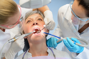 Senior woman patient dental check open mouth professional dentist team