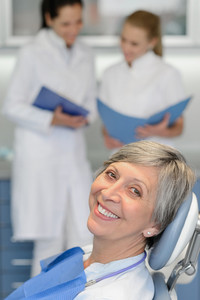 Senior woman patient with dentist team at dental surgery smiling