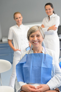 Senior woman patient with professional dentist team at dental surgery
