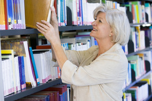 Senior woman pulling a library book off shelf