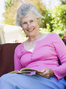 Senior woman reading book outside looking to camera