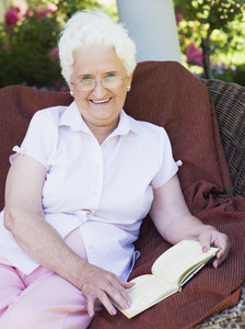 Senior woman reading book sitting on garden chair