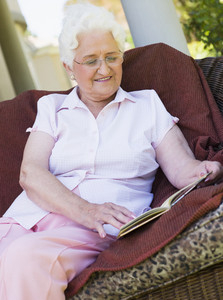 Senior woman reading book sitting on garden furniture