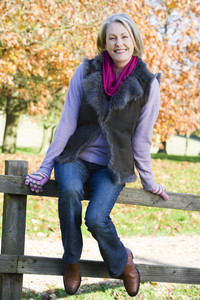 Senior woman sitting on fence with autumn trees in background